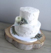 Rustic buttercream wedding cake on tree stump